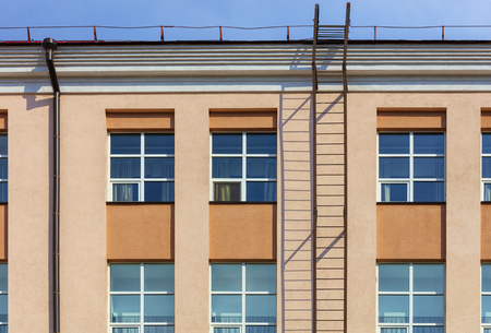 Photo pour Fragment of the facade and reconstruction of a residential building, fire escape frame overlooking the roof of the building. - image libre de droit