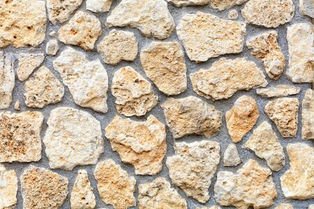 Texture and background of the wall of an old stone made of beige sandstone and coquina n the form of rough homogeneous masonry cobblestone.