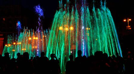 Photo pour Dark silhouettes of people around the fountainin the late evening, multi-colored neon lights illuminate the jets of a powerful urban singing fountain. - image libre de droit