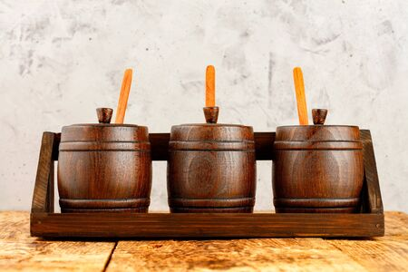 Photo pour Wooden decorative barrels for bulk cereals with wooden measuring spoons in them, lie in a wooden tray on an old wooden table against a background of gray concrete. - image libre de droit