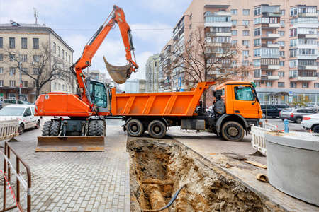 Photo pour Emergency road vehicles, an excavator and a truck are working on the repair of the heating main. A dug trench on the sidewalk of an autumn city street. - image libre de droit