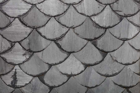 Photo pour The roof is made of gray slate slabs in the shape of fish scales. Background and texture, close-up. - image libre de droit