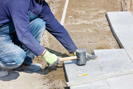 Photo for A worker in a blue overalls, half-crouched, strikes the granite blocks with a rubber mallet, assembling a new sidewalk onto the sandy base of the marked area. Close-up, selective focus, copy space. - Royalty Free Image