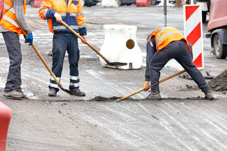 Photo for Traffic workers in bright orange reflective vests shovels road debris at the joints of the road sections being repaired. Copy space. - Royalty Free Image