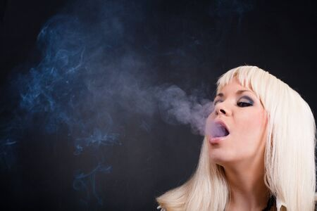 beautiful blonde smoking girl at black background