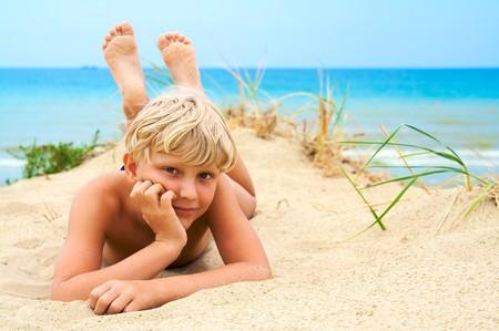 Photo pour Young blond boy lying on the beach - image libre de droit