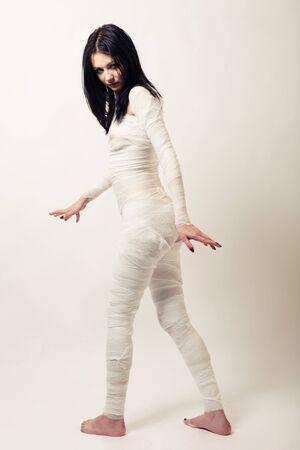 Girl dressed as a bandaged mummy turns a blind eye