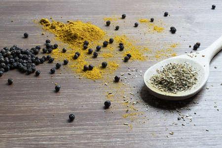 Foto für a wooden ladle with curry powder and pepper grain - Lizenzfreies Bild