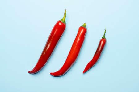 Foto für Some hot peppers on a colored surface - Lizenzfreies Bild