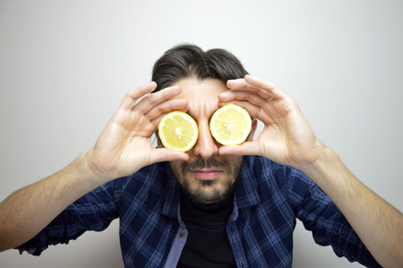 Foto de A curious young man covering his eyes with lemons discovering a new thing / new product - Imagen libre de derechos