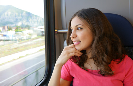 Foto de Young beautiful woman looking through the train window. Happy young woman sitting in the car. Modern people city lifestyle. Young urban woman. - Imagen libre de derechos
