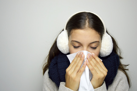 Flu or cold - sneezing woman sick blowing nose. Young woman being cold wearing earmuffs, scraf and sweater.