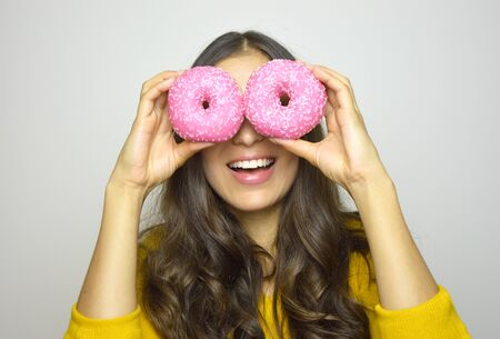 Foto de Smiling girl having fun with sweets isolated on gray background. Attractive young woman with long hair posing with donuts in her hands. - Imagen libre de derechos