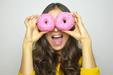 Foto de Close-up portrait of long-haired smiling girl having fun with sweets isolated on gray background. Attractive young woman with long hair posing with pink donuts in her hands - Imagen libre de derechos