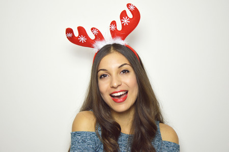 Foto de Happy beautiful woman with reindeer horns on her head looks at camera on white background. Christmas holidays. - Imagen libre de derechos