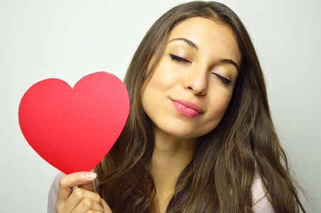 Foto de Valentine's Day. Sweet girl in love with closed eyes holding a paper heart and smile at camera on gray background. - Imagen libre de derechos