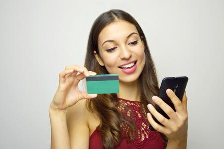 Foto de Happy smiling girl holding credit card in hand on white background. E-commerce woman. People doing shopping online. - Imagen libre de derechos