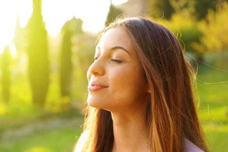 Photo pour Woman profile portrait breathing deep fresh air with nature in background - image libre de droit
