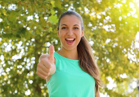 Photo pour Beautiful fitness woman agreement with thumb up outdoor with a green unfocused background. - image libre de droit