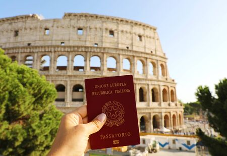 Photo pour Citizenship concept: hand hold Italian passport in front of Colosseum in Rome. - image libre de droit