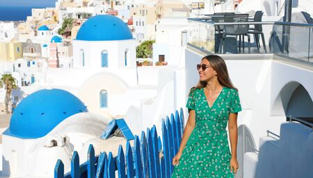 Photo pour Travel in Europe. Happy cheerful girl enjoying holidays in Greece. Beautiful tanned woman with sunglasses visiting Oia village in Santorini island, Greece. - image libre de droit