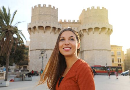 Photo pour Smiling beautiful tourist girl in Valencia, Spain. Attractive young woman with Torres de Serranos gate of Valencia on the background. - image libre de droit