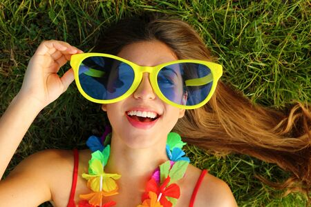 Photo pour Close up of girl wake up lying on grass after Carnival party. Portrait of pretty young woman with big funny sunglasses and carnival garland. - image libre de droit