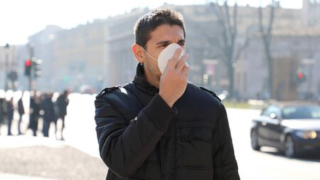 Photo pour COVID-19 Man in city street wearing face mask protective for spreading of disease virus: Coronavirus Disease 2019. Close up man with surgical mask on face against SARS-CoV-2. - image libre de droit