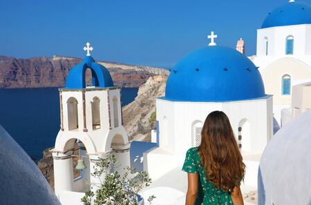 Photo for Tourism in Greece. Back view of traveler tourist girl visiting the famous white village with blue domes of Oia, Santorini. European travel destination. - Royalty Free Image