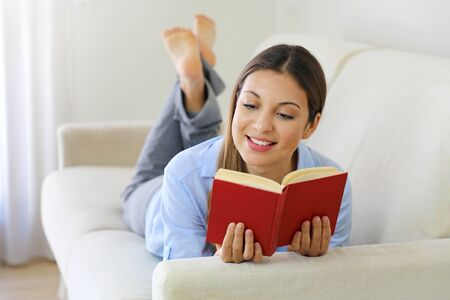 Photo pour Happy teen girl lying on sofa in the living room while reading her favorite author of books - image libre de droit
