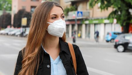 Photo pour COVID-19 Pandemic Coronavirus Woman in city street wearing KN95 FFP2 mask protective for spreading of disease virus SARS-CoV-2. Girl with protective mask on face against Coronavirus Disease 2019. - image libre de droit