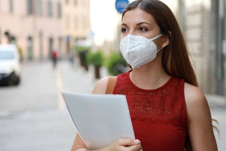 Photo for COVID-19 Global Economic Crisis Unemployed Worried Girl with KN95 FFP2 Mask  Looking for Job Walking in City Street Delivering Curriculum Vitae - Royalty Free Image