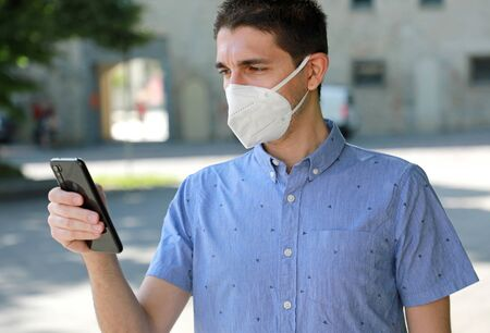 Photo pour COVID-19 Mobile Application Young Man Wearing KN95 FFP2 Mask Using Smart Phone App in City Street to Aid Contact Tracing and Self Diagnostic in Response to the Coronavirus Pandemic 2019 - image libre de droit