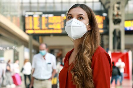 Photo pour Traveler woman wearing KN95 FFP2 face mask at the airport. Young caucasian woman with behind timetables of departures arrivals waiting worried information for her flight. - image libre de droit