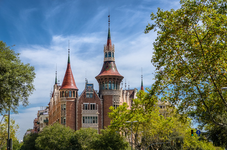 View on fabulous Casa de les Punxes house in green trees and blue sky, Barcelona Spain