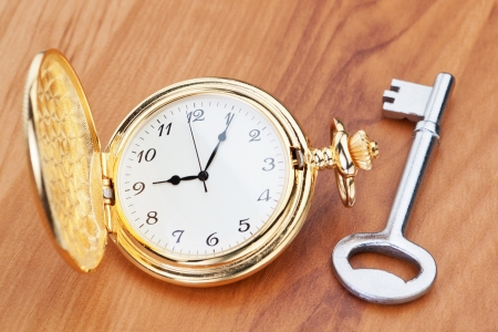 Gold pocket watch and key  Against the background of a wooden texture