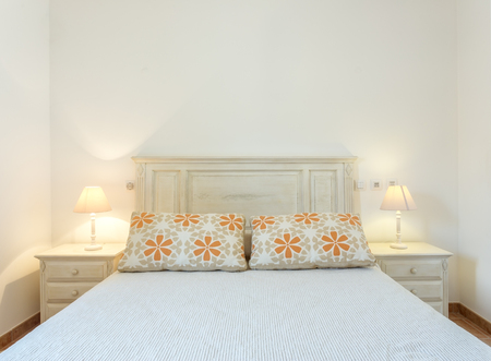 Modern bedroom with lampshades, photographed frontally.