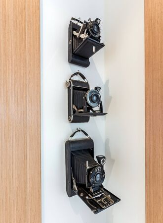 Photo for Vintage cameras with a black, leather case hanging in a corner on a white wall. - Royalty Free Image