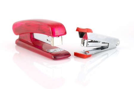Two staplers over white