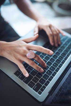 Foto de girl's hands with a rose quartz heart-shaped ring prints on a laptop - Imagen libre de derechos