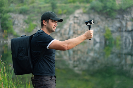 Photo pour Side view of traveller holding stabilizer for camera while taking photo. He wearing in black T-shirt and baseball cap - image libre de droit
