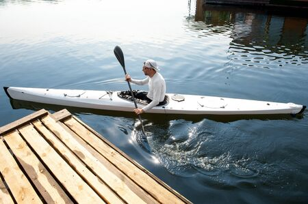 Foto de Active hobby concept. New white canoe with paddle man departing from the pier - Imagen libre de derechos
