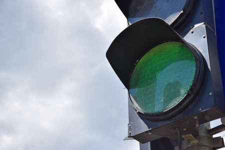 Photo for On the right side of the frame, there is a traffic light with a glowing green light against the sky. There is a place on the left for an inscription - Royalty Free Image
