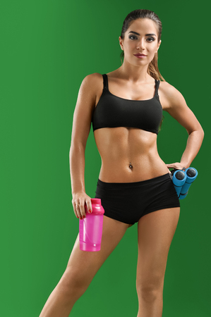 Attractive young fitness woman with a sports bottle on green bac