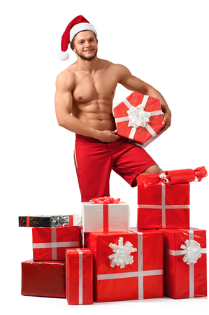 Sexy Santa Claus man with a pile of presents