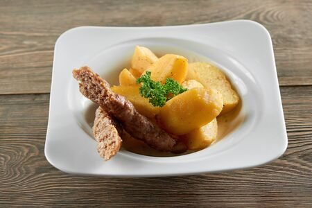 Little portion of fried potatoes with sausage and parsley