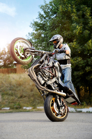 Ivano-Frankivsk, Ukraine - 28 August 2015 : Confident biker performing extreme stunts on sport motorcycle . Man stands on one backwheel of bike on the road near green trees on background..