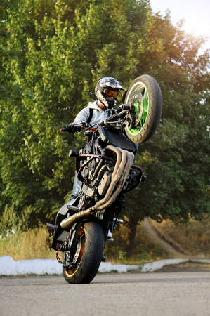 Ivano-Frankivsk, Ukraine - 28 August 2015 :Portrait of a male biker showing off tricks on a motorcycle during sunny day. Stunt performer is standing on back wheel of his sport bike.