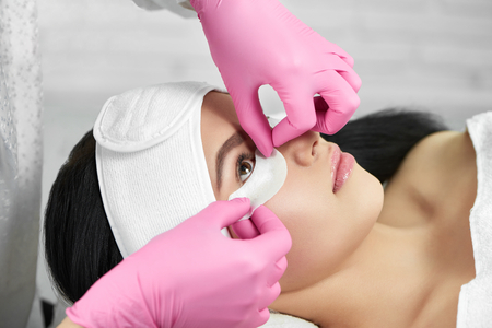 Photo pour Lashmaker is prepearing girl for lashes extension. Salon procedure of lashes enhancement. Professional wearing pink hygienic gloves. Client lying on special coach wearing headbandage for lashmaking. - image libre de droit