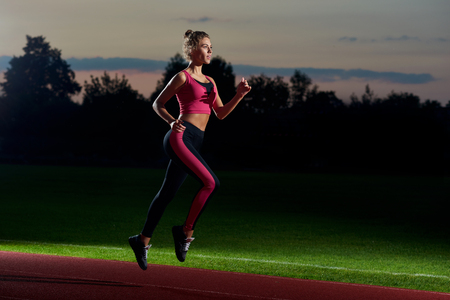 Foto de Side view of pretty and athletic girl in stylish black and pink sport wear running at night on stadium track. Woman preparing and training for first marathon. Concept of healthy and sport activity. - Imagen libre de derechos